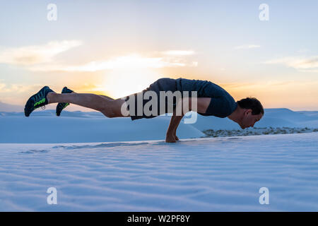 Man exercising doing shelf exercise balancing on fists in white sands dunes national monument in New Mexico view of sunset - Stock Photo