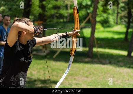 Nis, Serbia - June 16. 2019 Professional girl archer with bow shoot arrow in the forest on knight festival and tournament. Bowman before shooting - Stock Photo