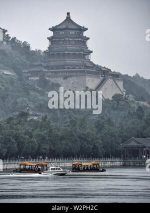 Beijing, China. 10th July, 2019. Visitors take boats on the Kunming Lake during a rainfall in the Summer Palace in Beijing, capital of China, on July 10, 2019. Credit: Li Xin/Xinhua/Alamy Live News - Stock Photo