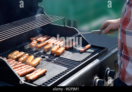 Man cooking hot dogs and smoked sausages on a propane BBQ - Stock Photo