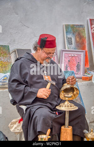 Mertola, Portugal - May 18, 2019: Moroccan craftsman carving beautiful metal objects in the streets of Mertola, where the Islamic festival is held eve - Stock Photo