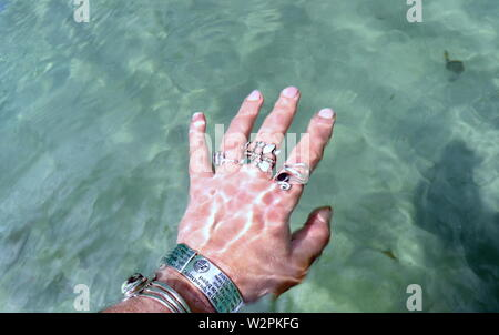 Woman's hand with silver bracelets and rings, splashing in ocean water - Stock Photo