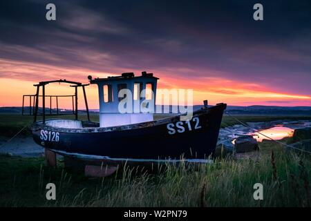 Tug boat marooned in estuary with gorgeous sunrise behind.  Surrounded by Welsh hillside - Stock Photo