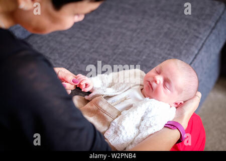 A tiny, newborn baby boy lying on a womans' lap holding her finger.  The baby is peacefully asleep, wrapped up in a cardigan - Stock Photo