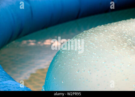 drops in the light - on the surface of an inflatable toy wheel - Stock Photo