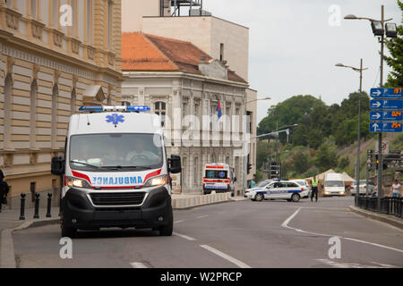 Ambulance vehicle on the street, with Police in background, securing public event in Belgrade - Stock Photo