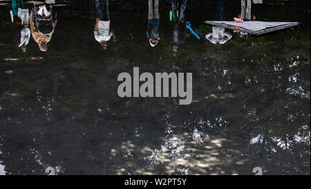 Berlin, Germany. 10th July, 2019. Visitors stand at the pond on the grounds of the memorial for the Sinti and Roma murdered in the National Socialist era in Tiergarten. Previously unknown perpetrators damaged a glass pane on the monument in the evening. The State Security Police are investigating. Credit: Paul Zinken/dpa/Alamy Live News - Stock Photo