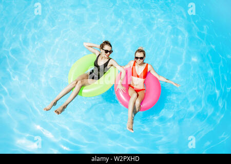 Two women swimming on the inflatable rings, relaxing in the water pool outdoors during the summer time, View from above - Stock Photo