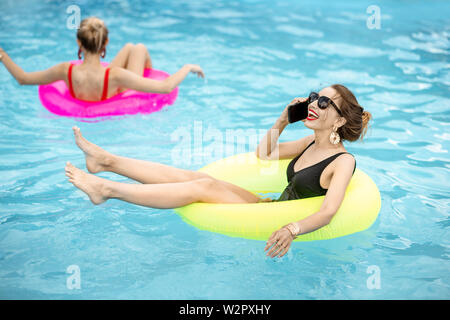 Young woman talking with phone while swimming with inflatable ring in the water pool outdoors during the summertime - Stock Photo