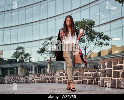Smiling young woman using cellphone outdoors in the city - Stock Photo