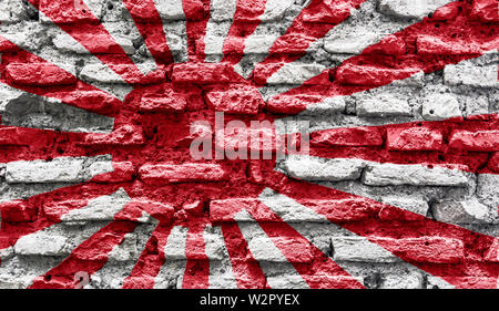 The japanese Rising Sun Flag imprinted on an old brick wall - Stock Photo