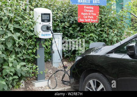 Electric car being charged in a public car park, UK. Electric charging point. - Stock Photo