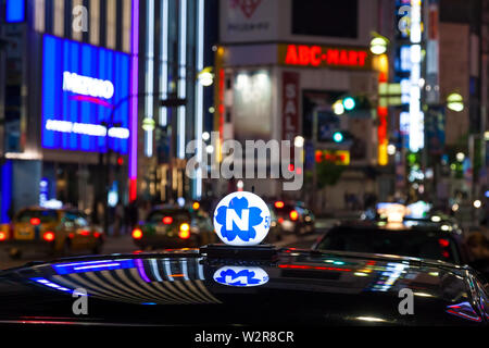 Roof of taxi and neon advertising signs at night in Shinjuku District, Tokyo, Japan. - Stock Photo