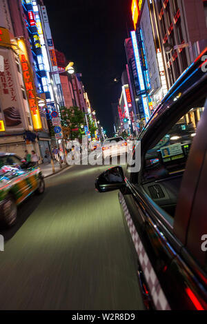 Motion blurred view from taxi of street and neon advertising signs at night in Shinjuku District, Tokyo, Japan. - Stock Photo