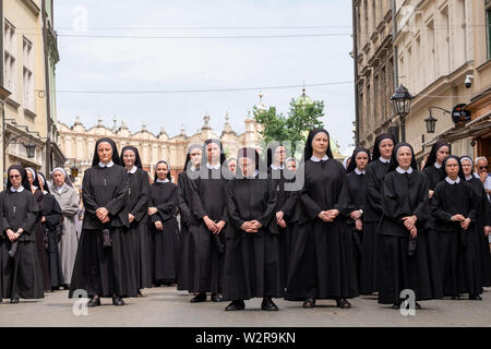 Nuns taking part in a procession for the Feast of Corpus Christi, in the streets of Krakow old town, Poland, near the Main Market Square. - Stock Photo