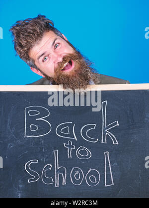 Continue your education with us. Teacher invites to continue studying. New semester in school. Teacher bearded man stands and holds blackboard with inscription back to school blue background. - Stock Photo