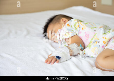 Asian baby boy sleeping on bed with infusion set at child department in the hospital. Children with infectious diseases IPD, Invasive Pneumococcal Dis - Stock Photo