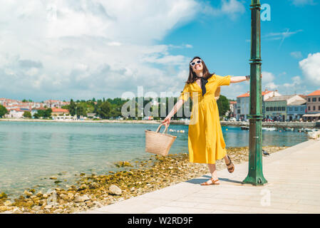 woman walking by sea quay in summer day in yellow sundress - Stock Photo