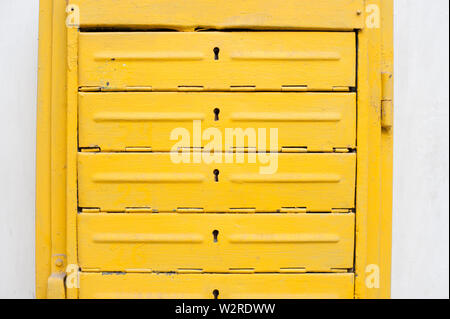 old vintage yellow iron letterbox on white wall - Stock Photo