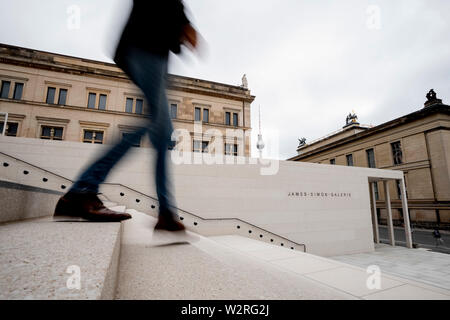 Berlin, Germany. 10th July, 2019. A man walks down the stairs of the James Simon Gallery before a press conference for its upcoming opening. In the background you can see the New Museum (l-r) of the Berlin Television Tower and the Old Museum. The museum entrance building, named after the patron of the Berlin museums James Simon, houses an information and cash desk area, cloakroom, museum shop, lecture hall, exhibition area and a café-restaurant. (Wiping effect due to long exposure time) Credit: Christoph Soeder/dpa/Alamy Live News - Stock Photo