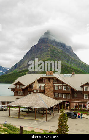 The porte-cochere of Many Glacier hotel with Grinnell Point in the background, Many Glacier Hotel, Glacier Park, Montana, Rocky Mountains, USA.