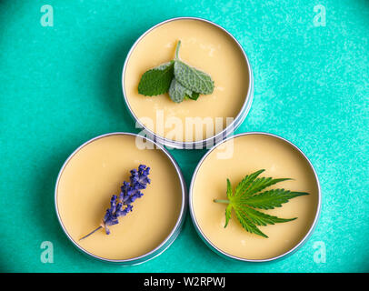 Cannabis salve made from hemp and CBD oils with mint, lavender and marijuana leaves on green background - Stock Photo