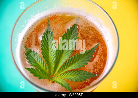 Detail of cold glass of beer with cannabis leaf, marijuana infused beverage concept - Stock Photo