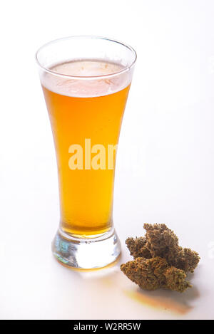 Detail of cold glass of beer with cannabis leaf and nugs isolated over white, marijuana infused beverage concept - Stock Photo