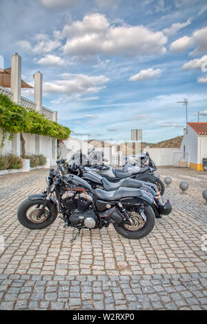 Mertola, Portugal - May 18, 2019: Motorcycles parked on a street in the beautiful city of Mertola, in the Portuguese Alentejo - Stock Photo