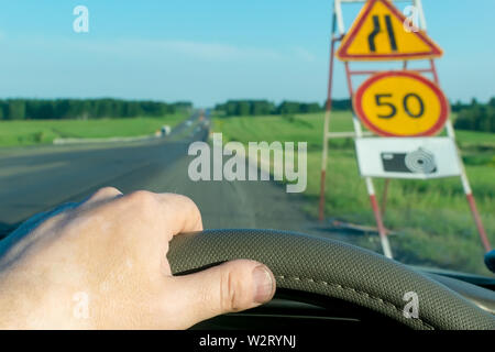 The driver's hand on the steering wheel of the car on the background of a suburban highway on the background of a road sign with speed limit - Stock Photo