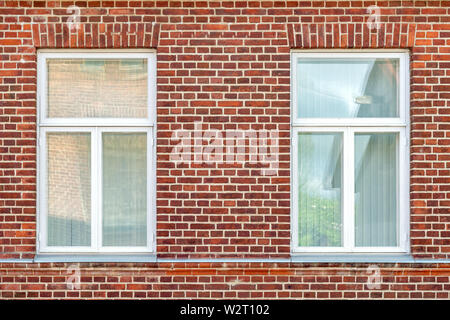 Two rectangular windows with white frames on a red brick wall background. From the window series of the world. - Stock Photo