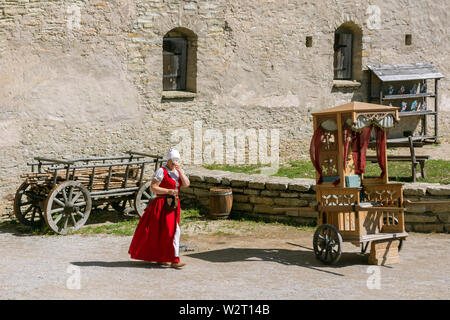 Rakvere, Estonia, June 28: View of the inner courtyard of the ancient castle in the city of Rakvere with a woman walking through it in a national red - Stock Photo