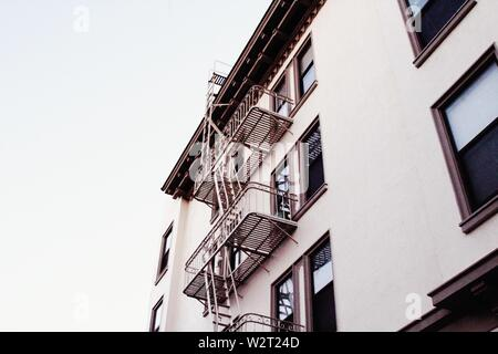 A low angle shot of a white concrete apartment building with stairs in San Francisco - Stock Photo