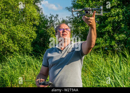 the man with the glasses starts with the hands of the quadcopter on the background of blue sky and greenery - Stock Photo