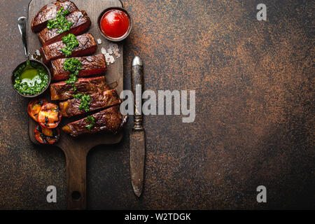 Grilled/fried and sliced marbled meat steak with fork, tomatoes, different sauces on wooden cutting board, top view, close-up with space for text, rus - Stock Photo
