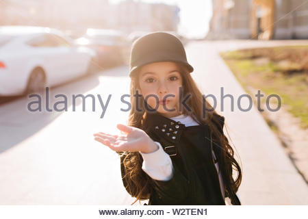 Surprised little girl funny posing waving hand, while spending time on the street in sunny morning. Portrait of lovely girlie wearing white shirt under black jacket standing on car background. - Stock Photo