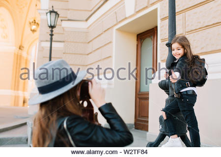 Lovely schoolgirl with black backpack gladly posing on the street leaning to the iron tube and showing thumb up. Elegant woman in vintage hat making photo of little daughter during walk around city. - Stock Photo
