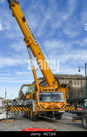 BUDAPEST, HUNGARY - MARCH 2018: Wide angle view of a large mobile crane with telescopic jib extended on the riverfront in Budapest. - Stock Photo
