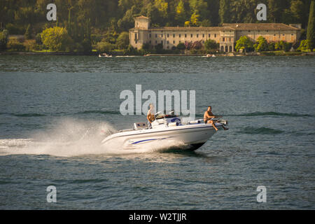 LAKE GARDA, ITALY - SEPTEMBER 2018:  Persons on a small motor boat at speed on Lake Garda. - Stock Photo