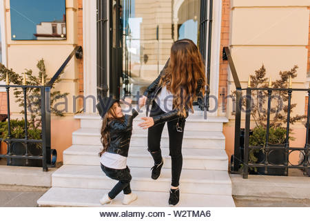 Outdoor portrait of playful little brunette girl in black hat standing with thumb up on the stairs. Shapely curly woman in stylish outfit comes out from store with cheerful smiling daughter - Stock Photo