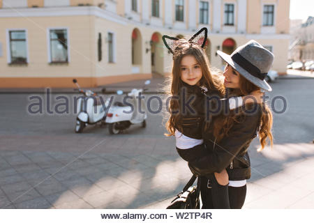 Trendy shapely woman with bag carrying curly brunette girl, smiling at camera. Portrait of young mother in stylish hat spending time with lovely daughter in weekend, going to shopping - Stock Photo
