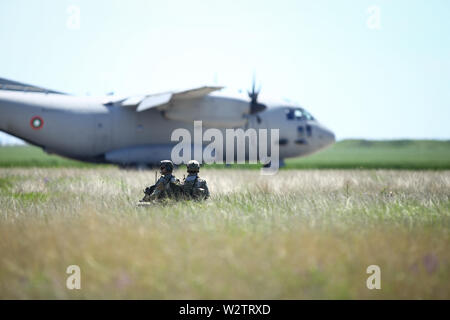 Boboc, Romania - May 22, 2019: Romanian army soldiers patrol on a military air base, with an Alenia C-27J Spartan military cargo plane from - Stock Photo