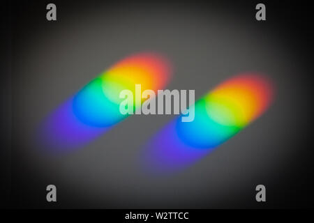 Rainbow Colours on the ceiling, caused by sunlight passing through small prisms on the windowsill. 'Colour & Texture'. The prisms come from binoculars - Stock Photo
