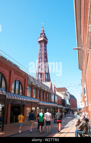 People walking down victoria street past the Houndshill shopping centre and enjoying a sunny day in Blackpool with Blackpool Tower in background - Stock Photo