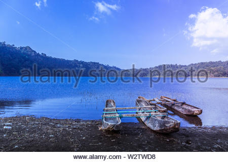 Fishing boats at blue hour on the shore of Lake Tamblingan in Bali, Indonesia - Stock Photo