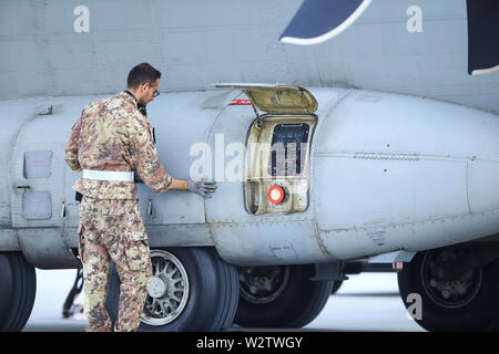 Otopeni, Romania - May 22, 2019: A mechanic is inspecting parts of an Alenia C-27J Spartan military cargo plane after landing on an airbase. - Stock Photo