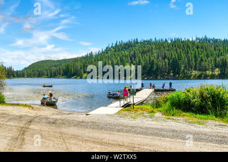 Families and friends gather at a small wooden boat ramp on Granite Lake as fishing boats enjoy a sunny day in North Idaho on the water. - Stock Photo