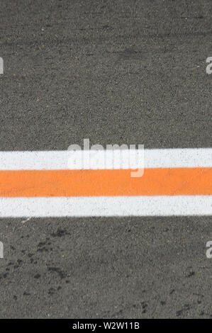 Asphalt colored background with a three horizontal stripes of white, orange and white horizontal that crosses the image in half - Stock Photo