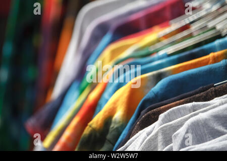 Closeup of multi-colored T-shirts hanging on hangers in the street, fair, secondhand, recycling concept - Stock Photo