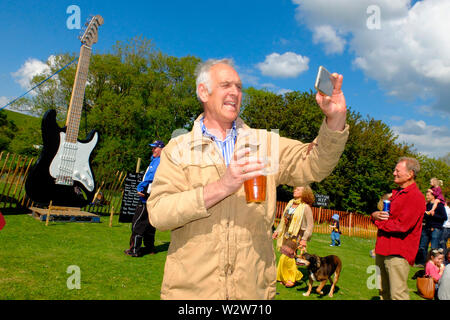 A man taking a selfie at Wolverton Folk and Blues Fair 2019 on the grounds of Wolverton Manor, Shorwell, Isle of Wight, England, UK. - Stock Photo